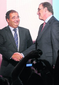 Banco Popular chairman Ron shakes hands with Banco Pastor chairman Arias  before a joint news conference in Madrid